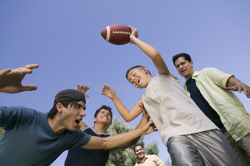 Boy (13-15) playing football with group of young men low angle view. royalty free stock image