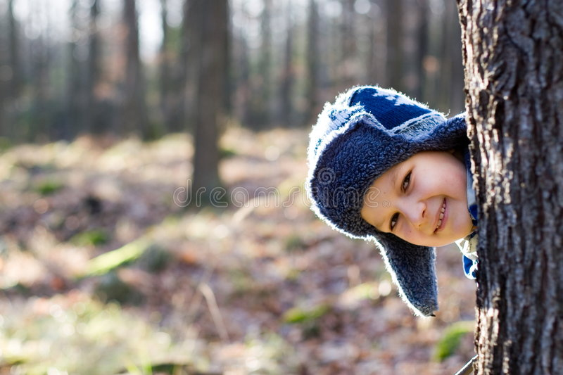 Boy Playing in a Forest. A smiling boy, wearing a blue winter hat, peeks his head around a tree while hiding and playing in a forest on a cold day royalty free stock photo