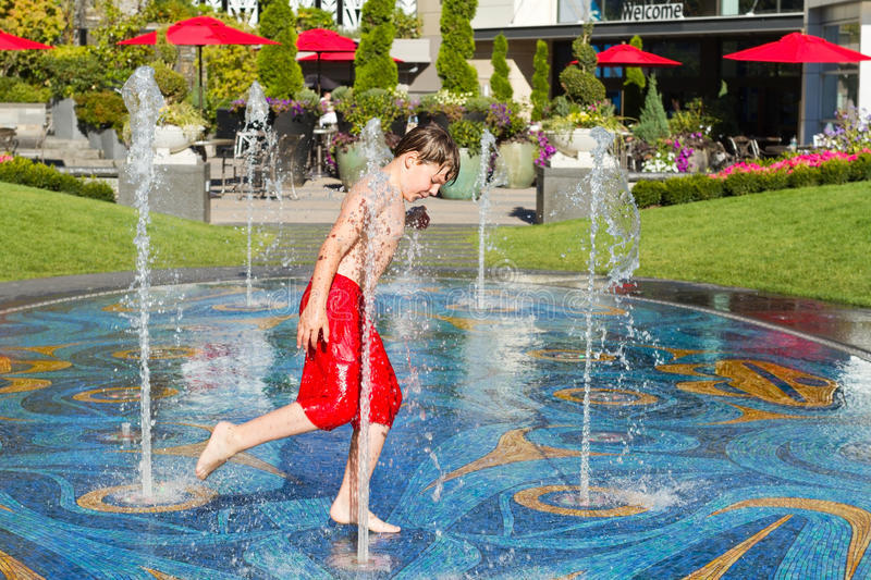 Boy playing in the fountain stock image