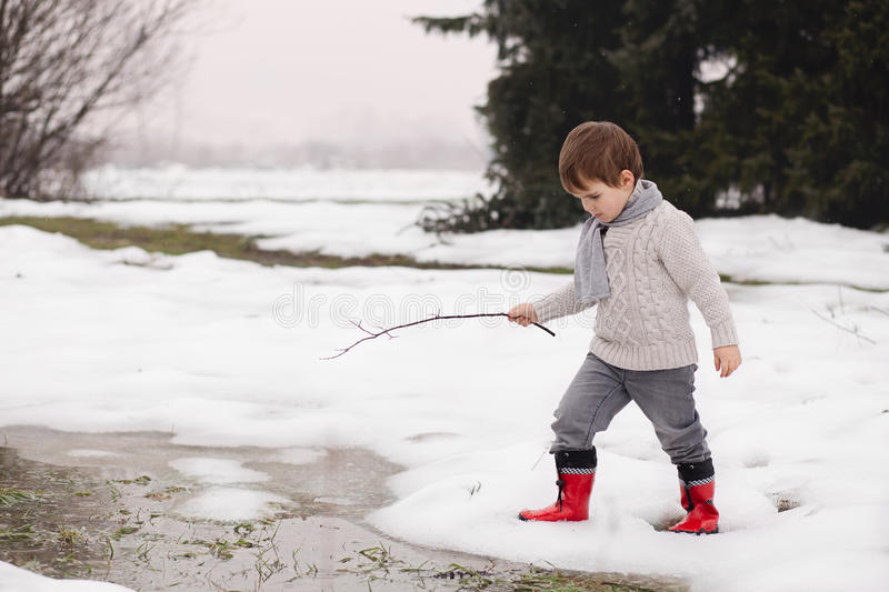 Boy playing with frozen water in winter stock photo
