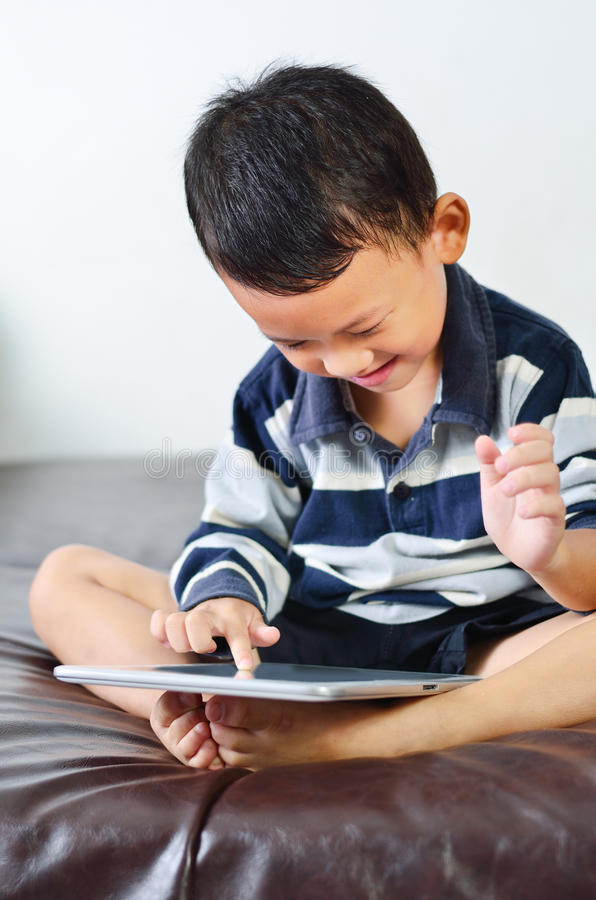 A boy playing a game on computer tablet. Close up a boy playing a game on computer tablet royalty free stock photos