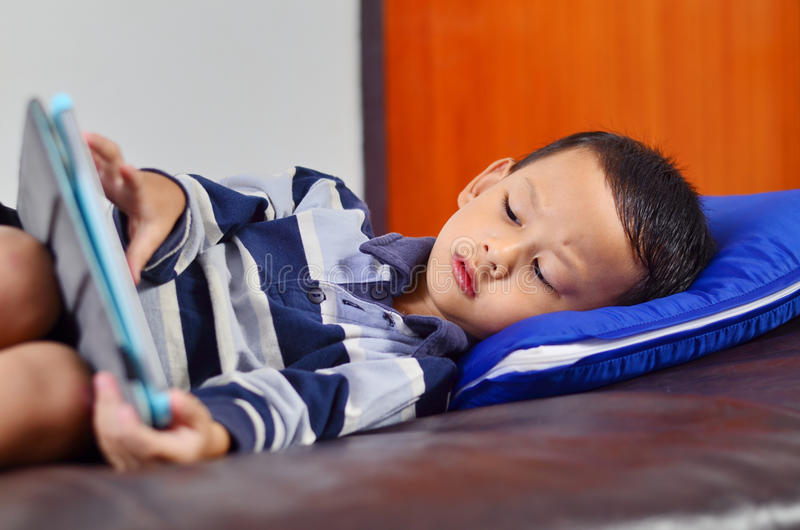 A boy playing a game on computer tablet. A boy looking and playing a game on computer tablet stock photography