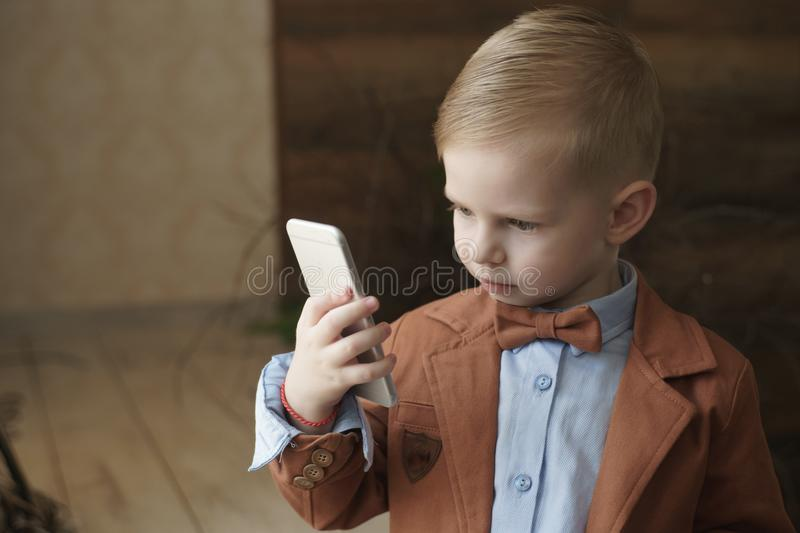 Boy playing in the game on the phone lying in bed next toy white teddy bear stock images