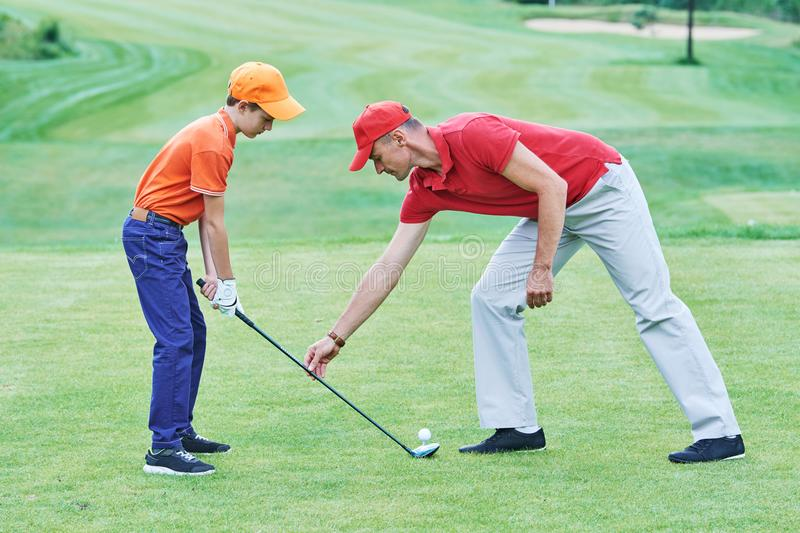 Boy playing golf in summer. Golf play. Boy player with instructor on green course field training in summer stock photos