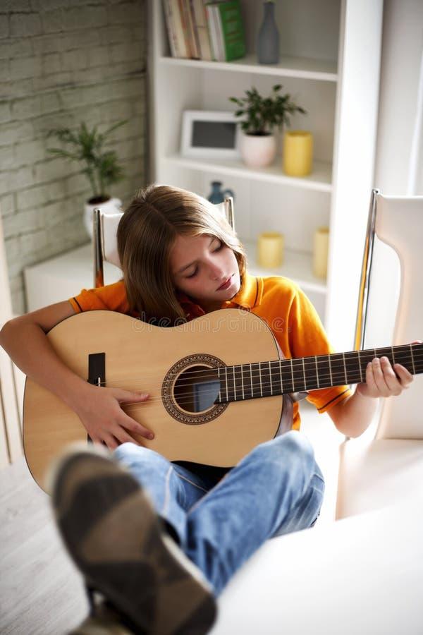 Boy playing guitar royalty free stock photos