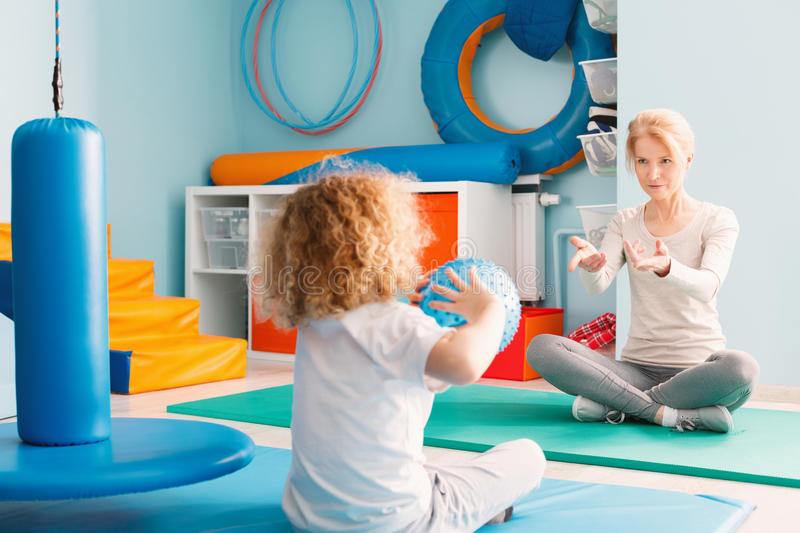 Boy playing with his therapist. Using a ball royalty free stock photos