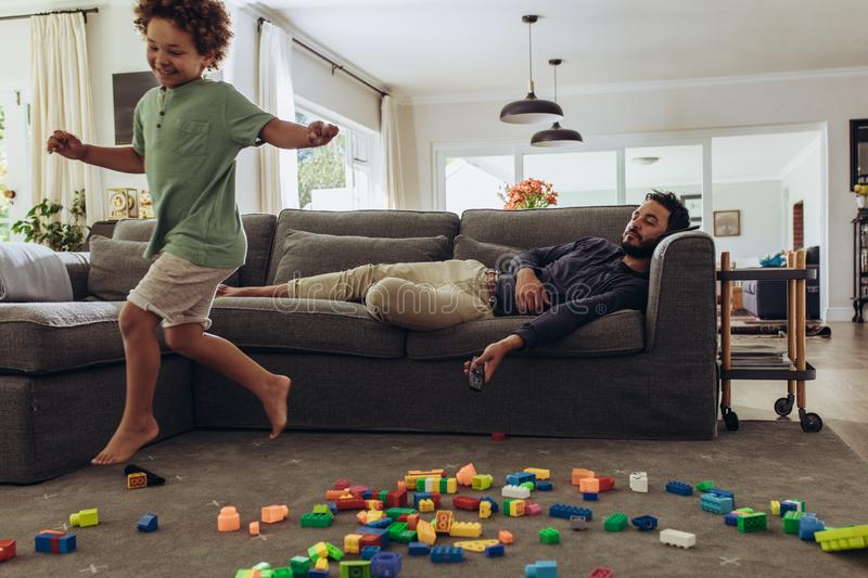 Boy playing at home while his father is sleeping royalty free stock image