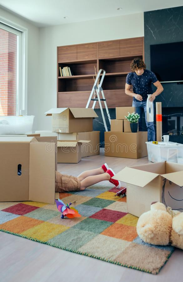 Boy playing inside a moving box while his father unpacks royalty free stock images
