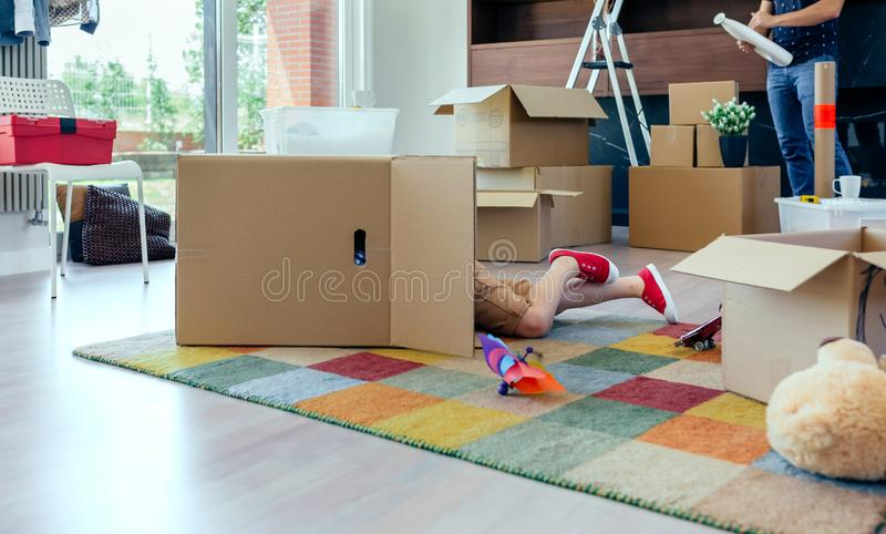 Boy playing inside a moving box while his father unpacks stock photo