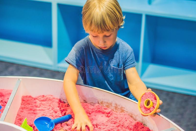 Boy playing with kinetic sand in preschool. The development of f. Ine motor concept. Creativity Game concept stock photos