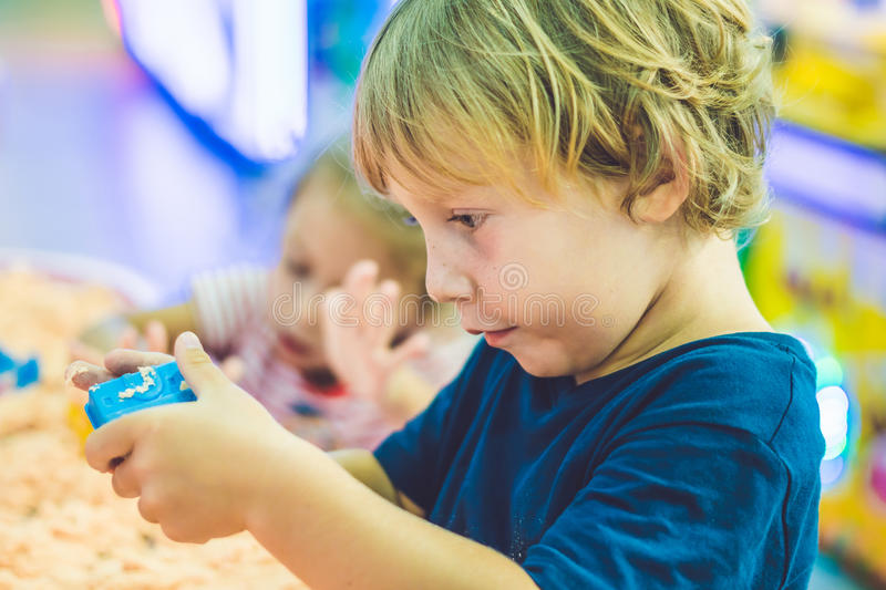 Boy playing with kinetic sand in preschool. The development of fine motor concept. Creativity Game concept.  royalty free stock image