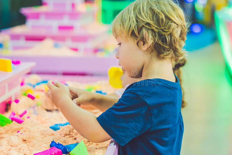 Boy playing with kinetic sand in preschool. The development of fine motor concept. Creativity Game concept.  stock photography