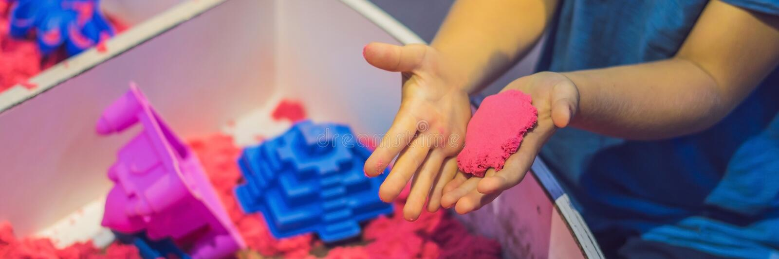 Boy playing with kinetic sand in preschool. The development of fine motor concept. Creativity Game concept BANNER, long. Boy playing with kinetic sand in stock photos