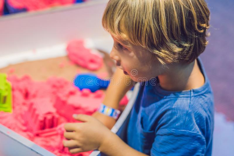 Boy playing with kinetic sand in preschool. The development of fine motor concept. Creativity Game concept.  royalty free stock photography