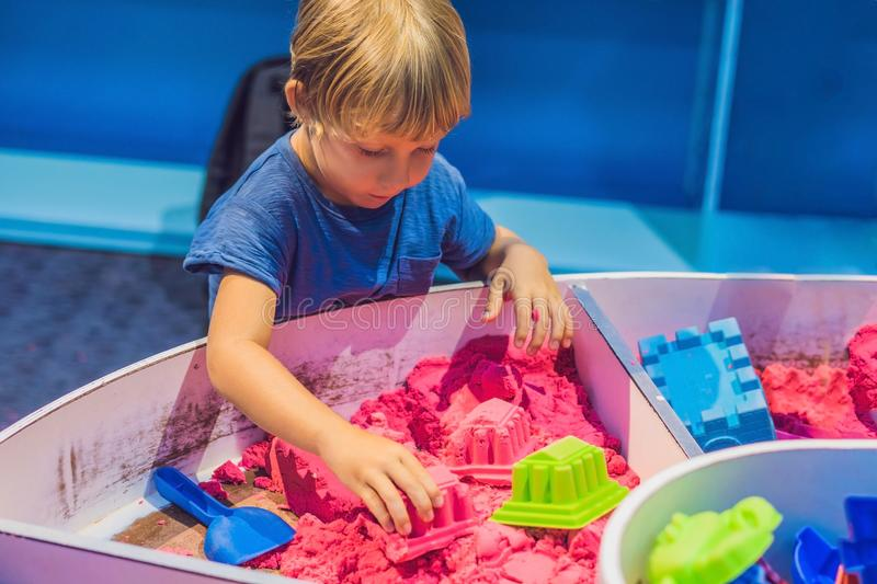 Boy playing with kinetic sand in preschool. The development of fine motor concept. Creativity Game concept.  stock images
