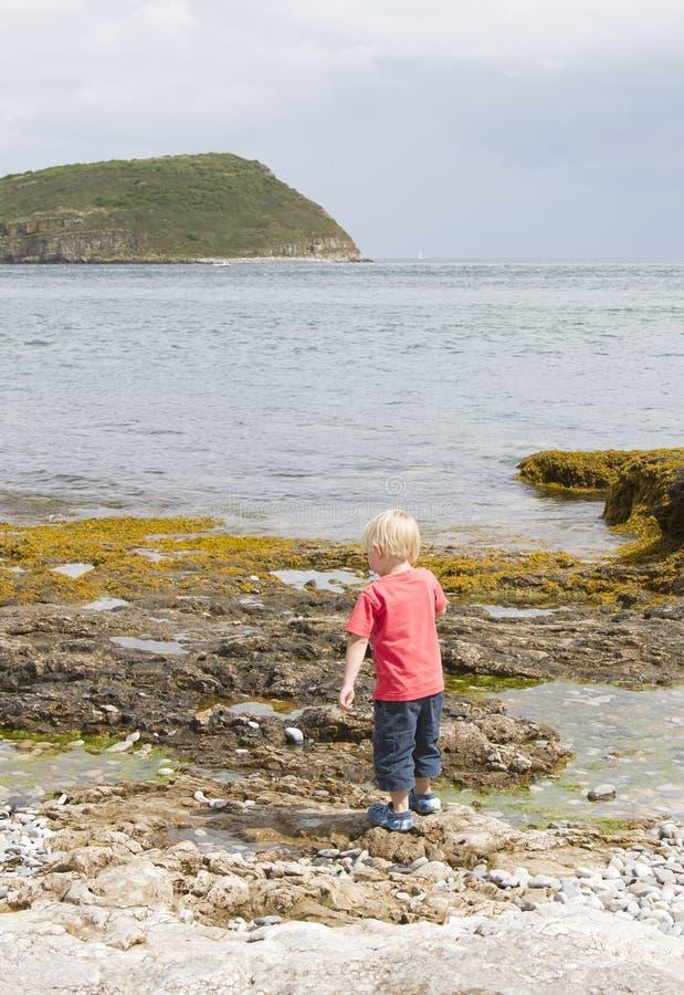 Boy playing near rock pools stock photos