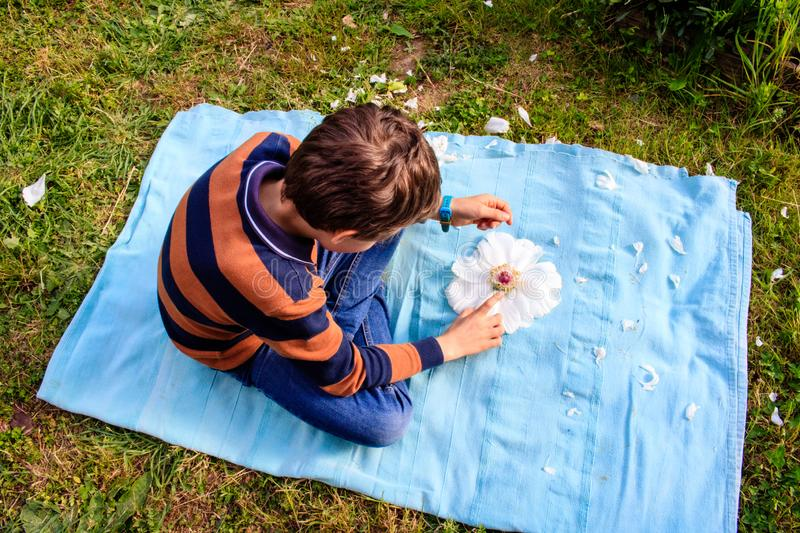 A boy playing outdoor wtih peony flower. Nature, ecology, childhood, environment design royalty free stock images