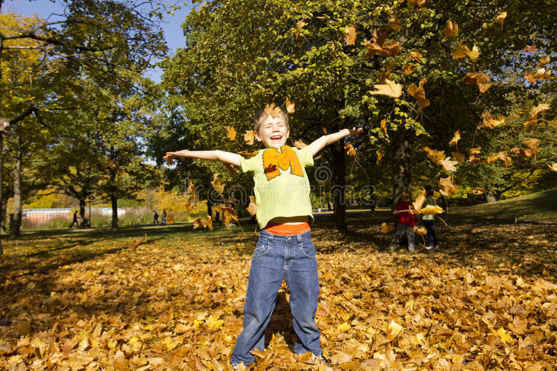 Boy playing outside with colorful leaves stock photo
