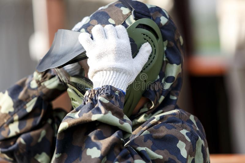 Boy is playing paintball on the field. two teams of paintball players in camouflage form with masks, helmets, guns on the field stock photos