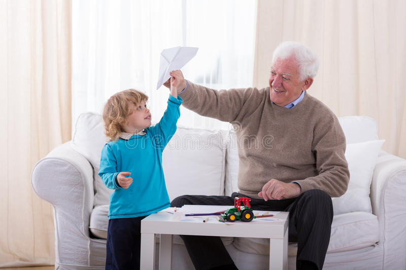 Boy playing with paper airplane. Grandpa and little boy playing with paper airplane royalty free stock photography