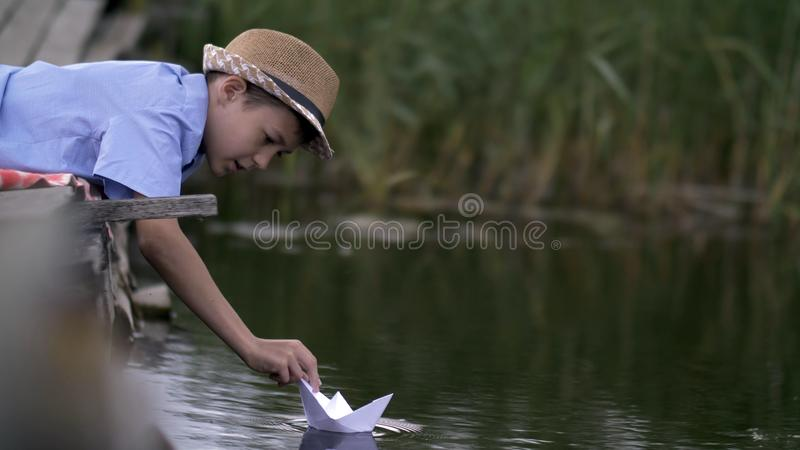 Boy playing with a paper boat in the lake on the pier royalty free stock image