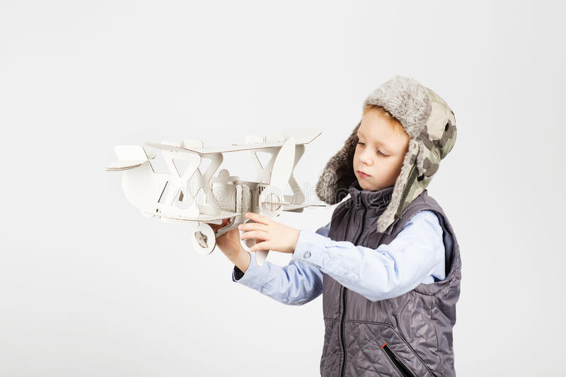 Boy playing with paper toy airplane and dreaming of becoming a p stock images