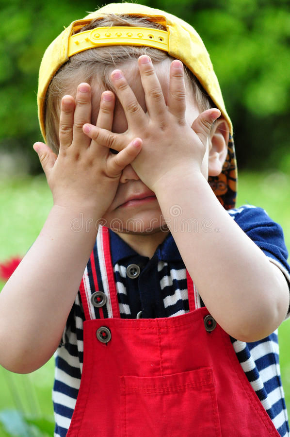 Boy playing peek-a-boo stock photos