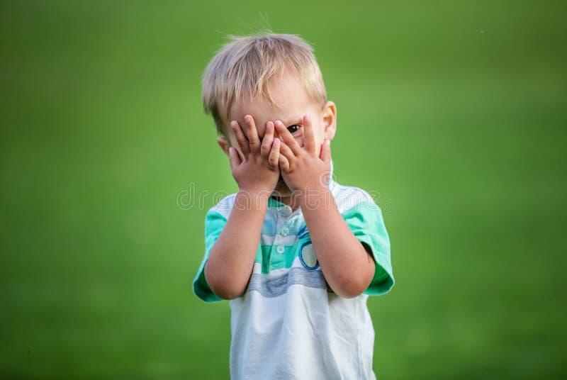 Boy playing peek-a-boo outdoors royalty free stock photo