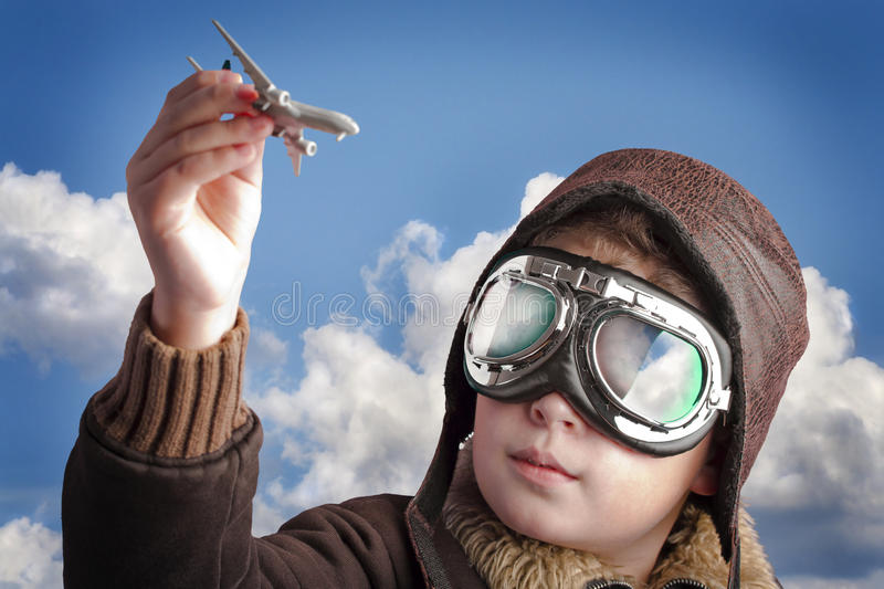 Boy playing with pilots hat and airport background stock photos