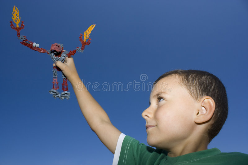 Boy playing with plastic robot royalty free stock images