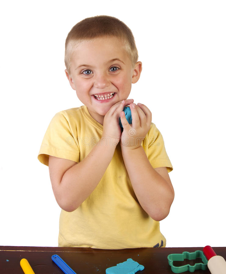 Boy playing with playdough stock images