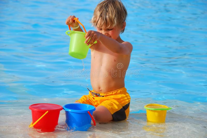 Boy playing in pool stock photos