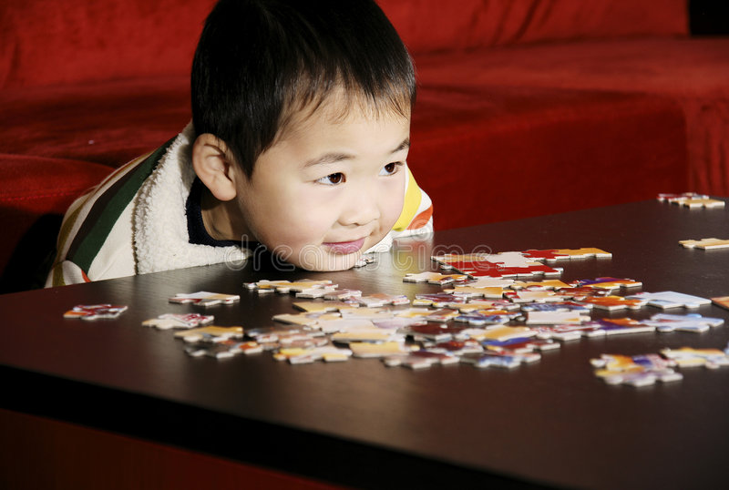 Boy playing puzzle game. A picture of a little chinese boy resting chin on table while playing puzzle game stock photo