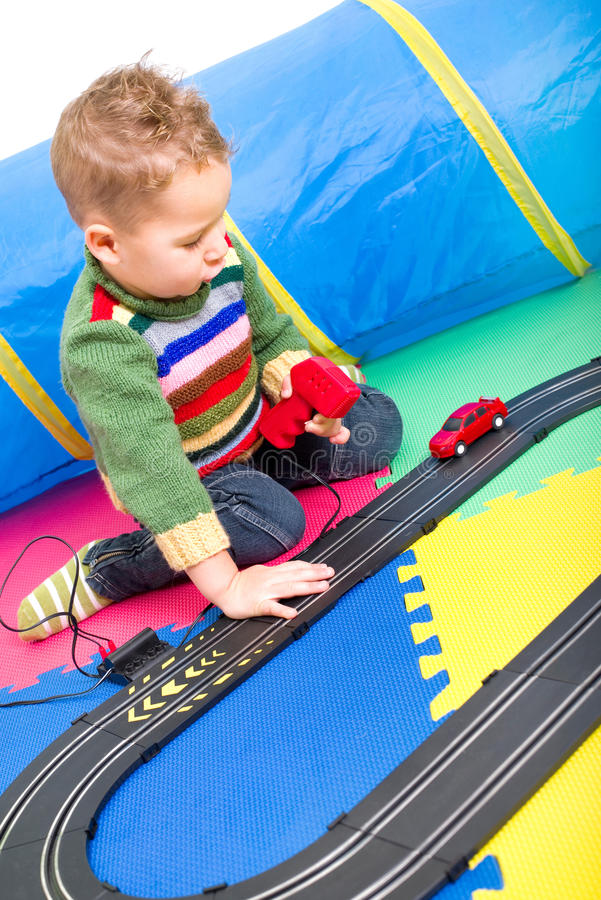 Boy playing with Racetracks. Little boy playing with a car race track stock photo