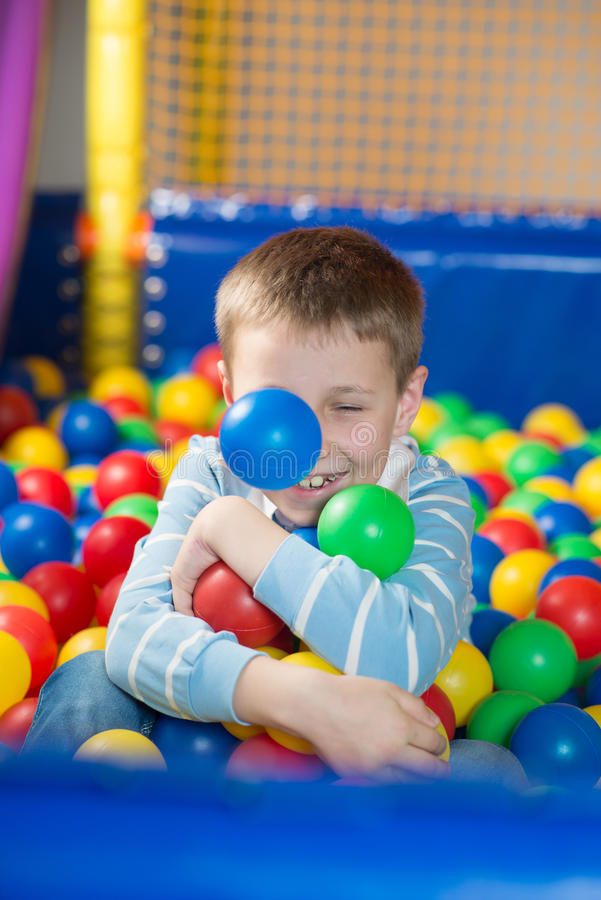 A boy in the playing room with many little colored balls. Close portrait stock image