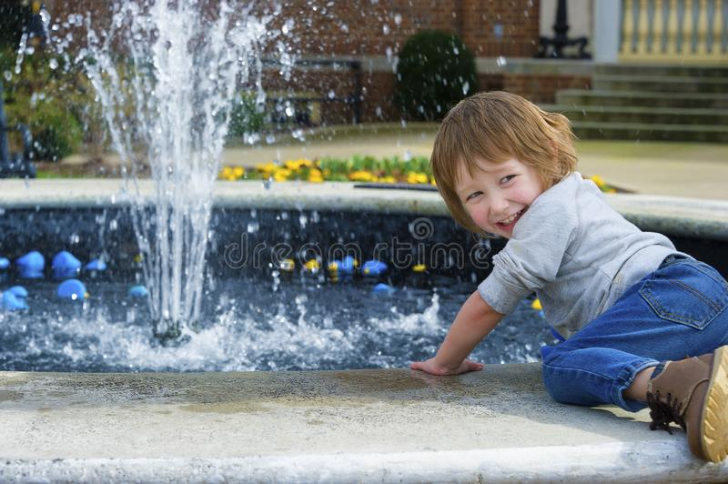 Boy playing with rubber ducks in fountain. Downtown Franklin, Tennessee, there is a fountain with lots of floating colorful ducks for children to play with stock image