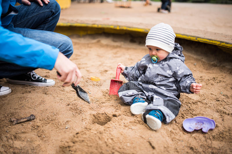Boy playing in the sand box with his father royalty free stock images