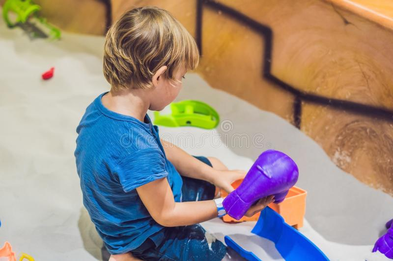 Boy playing with sand in preschool. The development of fine motor concept. Creativity Game concept.  stock images