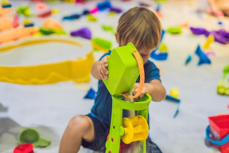 Boy playing with sand in preschool. The development of fine motor concept. Creativity Game concept.  stock photography