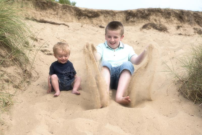 Boy playing in the sand with two year old baby brother stock photography