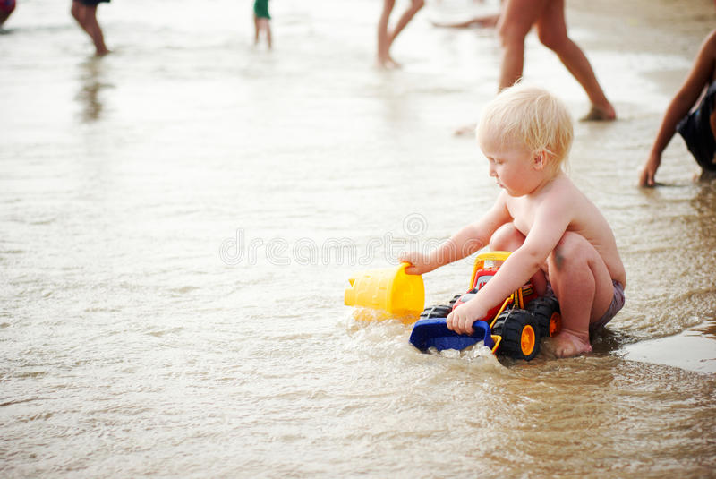 Boy playing in the sea. With a bucket and a tractor stock photos