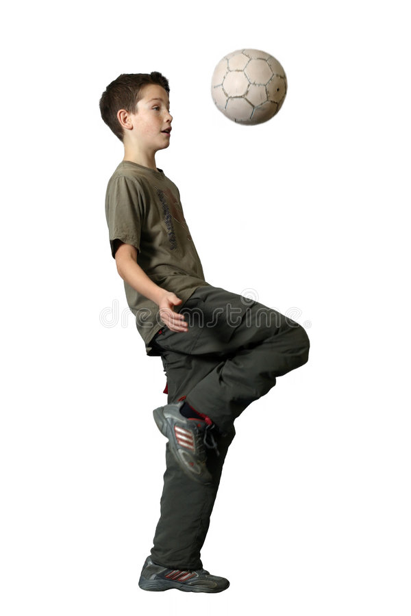 Boy Playing Soccer. Focus is on the face. A palm and a right foot and a ball are little blurred because of fast moving when playing royalty free stock image