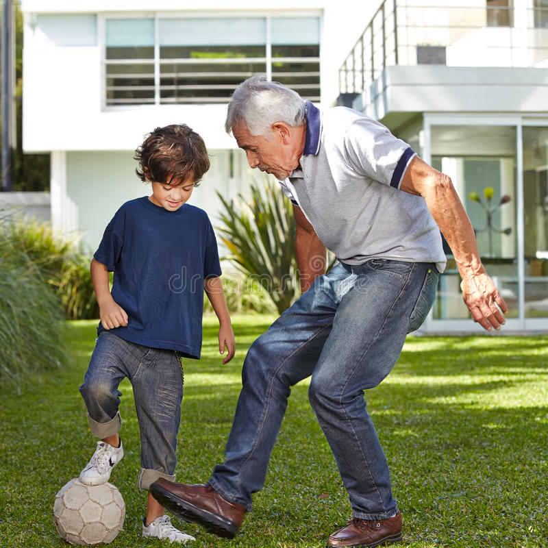 Boy playing soccer with grandfather stock photo