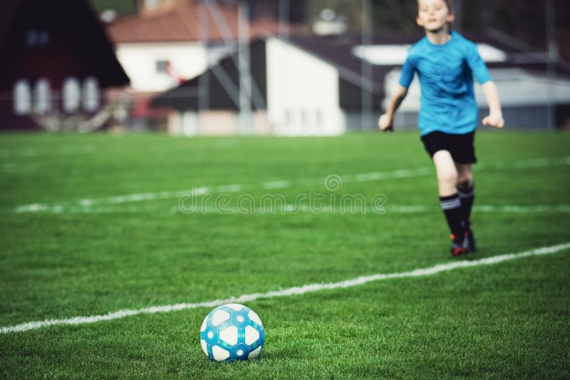 Boy playing soccer at local stadium outside on grass field running to kick the ball. Lower shot, focus on the ball. Children play. Ing football, favourite sport royalty free stock images