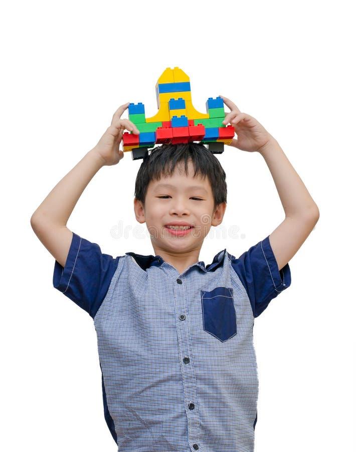 Boy playing spaceship block. Asian boy playing spaceship block over white royalty free stock image