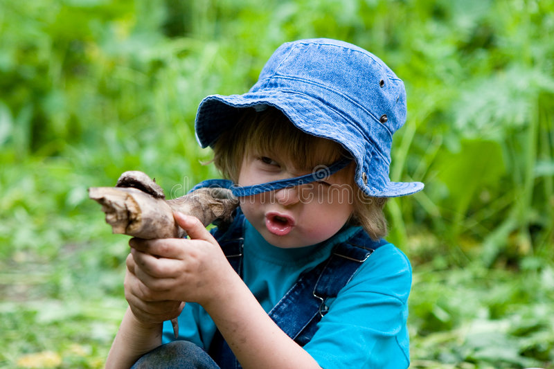 Boy playing with stick like with gun royalty free stock photography