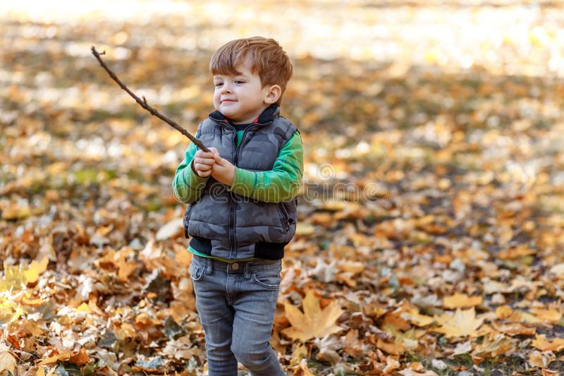 A boy playing with a stick outside stock images