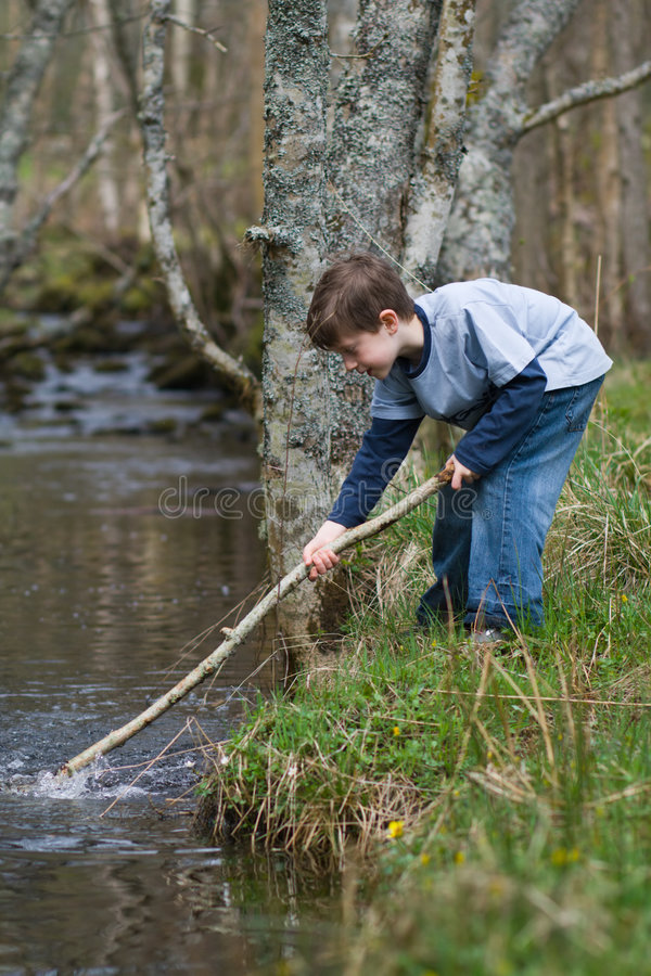 Boy playing in a stream stock photo