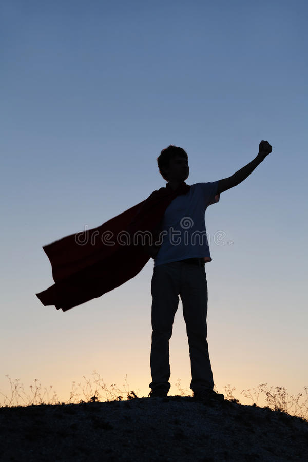 Boy playing superheroes on the sky background, silhouette of tee royalty free stock image