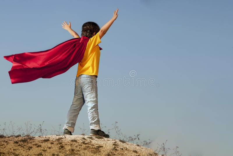 Boy playing superheroes on the sky background, teenage superhero stock photo